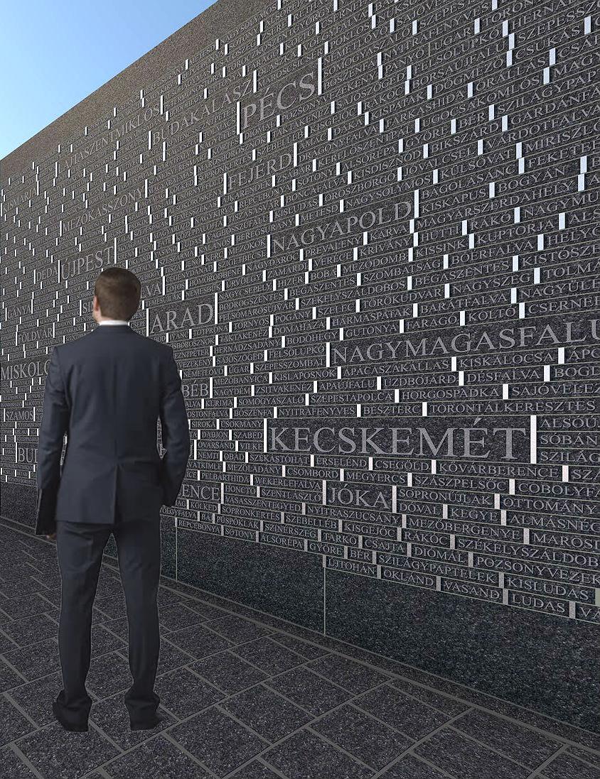Az Emlékhely egy részlete településnevekkel díszített fal előtt egy ember áll.